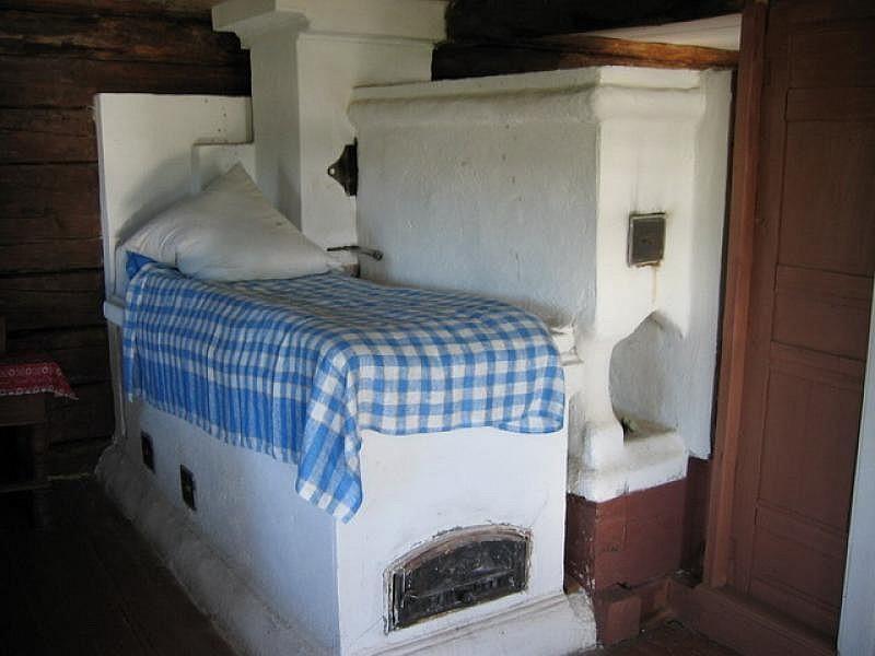 Белая кирпичная печь с лежаком-постелью