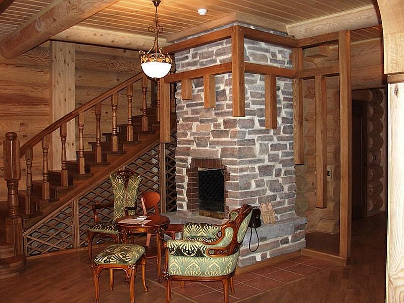 Каменный камин расположенный в доме около лестницы